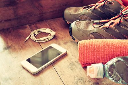 hombre comiendo: concepto de fitness con el teléfono móvil, toalla y calzado deportivo sobre fondo de madera .. visión superior