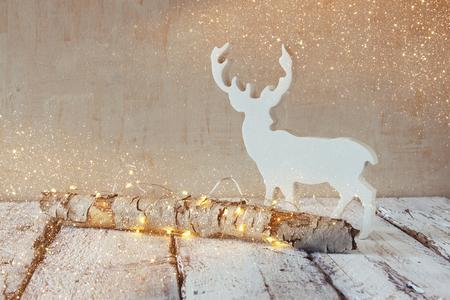 alte Baumstamm mit Fee Weihnachtsbeleuchtung und Rentiere auf Holz table.selective Fokus. Retro-gefilterte Bild mit Glitzer-Overlay