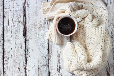 ropa de invierno: tapa de la vista de blanco acogedora jersey de punto con a taza de café en una mesa de madera Foto de archivo