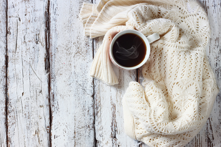 indoors: top view image of white cozy knitted sweater with to cup of coffee on a wooden table