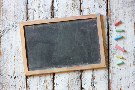 top image of chalkboard and colorful chalks over wooden table Stock Photo