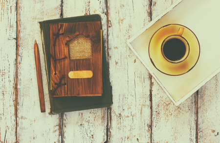 content writing: top view image of cup of coffee on wooden white tray and notebook, over wooden table. faded retro style filter