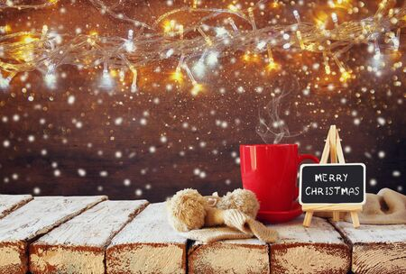 tea cosy: Cup of hot coffee and blackboard with words merry christmas written on it on wooden table in front of snowy garland lights background Stock Photo