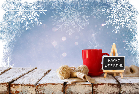 happy home: Cup of hot coffee and cozy knitted scarf and blackboard with words happy weekend written on it, on wooden table in front of glitter snowy background