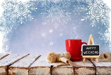 """Taza de café caliente y bufanda de punto acogedor y pizarra con las palabras """"feliz fin de semana"""" escrito en él, en la mesa de madera delante de brillo fondo cubierto de nieve"""