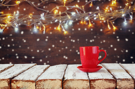tea cosy: Cup of hot coffee on wooden table in front of snowy garland lights background