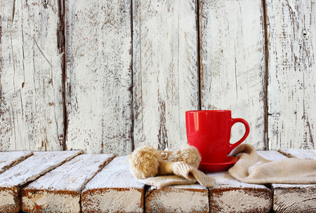 tea table: Cup of hot coffee and cozy knitted scarf on wooden table