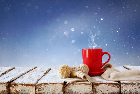 Cup of hot coffee and cozy knitted scarf on wooden table in front of glitter background