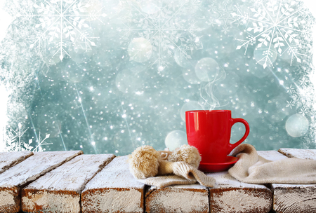 Cup of hot coffee and cozy knitted scarf on wooden table in front of glitter background with snowflakes overlay Stock Photo