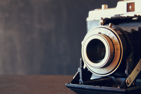 fashion: close up photo of old vintage camera lens over wooden table. selective focus
