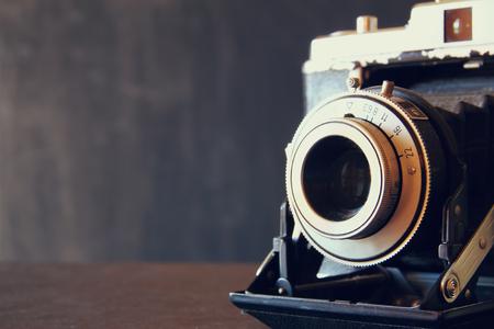 zblízka fotografie staré vinobraní objektiv fotoaparátu přes dřevěný stůl. selektivní zaměření