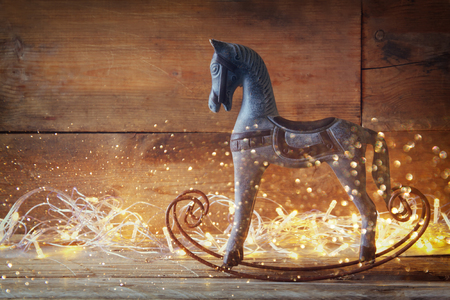 merry go round: double exposure image of rocking horse and magic christmas lights on wooden table