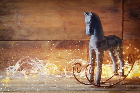 Doppelbelichtungsbild von Pferd und magische Weihnachtsbeleuchtung auf Holztisch Schaukel Lizenzfreie Bilder