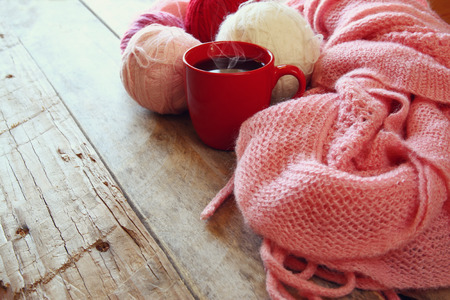 yarn: selective focus photo of pink cozy knitted scarf with to cup of coffee and wool yarn balls  on a wooden table. faded style retro filtered