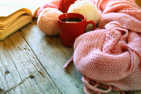 knit: selective focus photo of pink cozy knitted scarf with to cup of coffee, wool yarn balls  and open book on a wooden table Stock Photo
