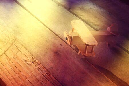 sencillez: foto abstarct de avión de juguete de madera sobre fondo de madera con textura. imagen de estilo retro. fotografiado sin aditing software, usando el filtro hecho a mano.
