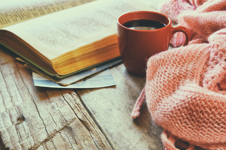 selective focus photo of pink cozy knitted scarf with to cup of coffee, wool yarn balls  and open book on a wooden table Standard-Bild
