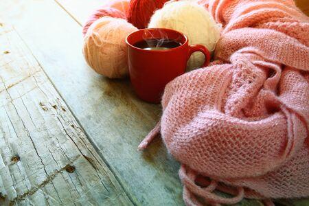 gomitoli di lana: messa a fuoco selettiva foto di rosa sciarpa a maglia accogliente con a tazza di caffè e filato di lana palline su un tavolo di legno. stile retrò sbiadita filtrato
