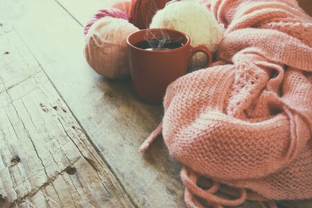 gomitoli di lana: selective focus photo of pink cozy knitted scarf with to cup of coffee and wool yarn balls  on a wooden table. faded style retro filtered