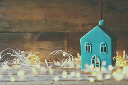 decorative house next to gold garland lights on wooden background. copy space