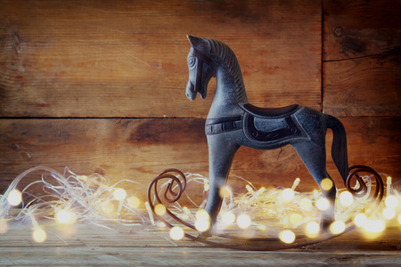 classic interior: image of rocking horse and magic christmas lights on wooden table