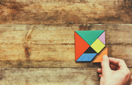 missing piece: mans hand holding a missing piece in a square tangram puzzle, over wooden table.