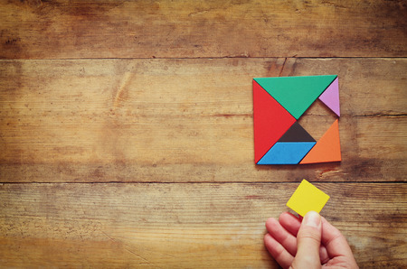 squares: mans hand holding a missing piece in a square tangram puzzle, over wooden table.
