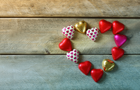 valentine          s day candy: top view image of colorful heart shape chocolates on wooden table. valentines day celebration concept. retro filtered ans toned image Stock Photo