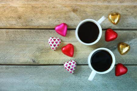 cafe bombon: top view image of colorful heart shape chocolates and couple mugs of coffee on wooden table. valentines day celebration concept. retro filtered ans toned image Foto de archivo