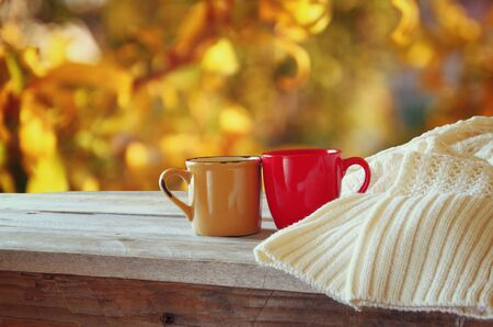 cup of tea: front image of two coffee cups over wooden table and woolen sweater in front of autumnal sunset background. Valentines Day concept