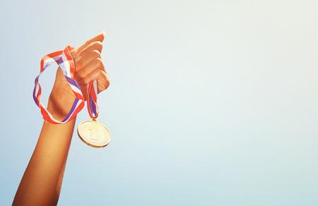 premios: Mujer mano levantada, sosteniendo la medalla de oro contra el cielo. premio y la victoria concepto Foto de archivo
