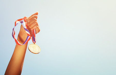 winning business woman: woman hand raised, holding gold medal against sky. award and victory concept