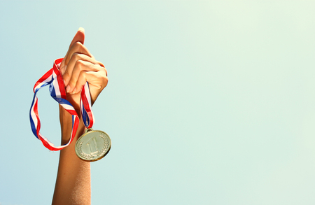 woman hand raised, holding gold medal against sky. award and victory concept