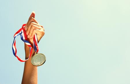 mujer deportista: Mujer mano levantada, sosteniendo la medalla de oro contra el cielo. premio y la victoria concepto Foto de archivo