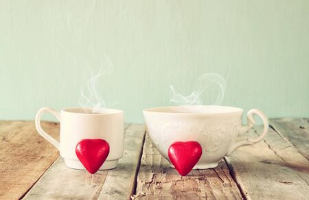 cafe bombon: image of tow red heart shape chocolates and couple cups of coffee on wooden table. valentines day celebration concept. vintage filtered Foto de archivo