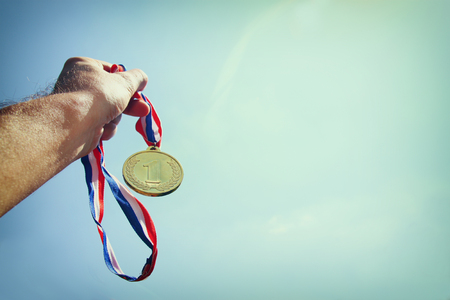 gold medal: man hand raised, holding gold medal against Sky. award and victory concept. selective focus. retro style image.