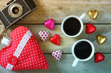 cafe bombon: Imagen de la visión superior de chocolates en forma de corazón, corazón colorido de la tela, cámara de fotos de época y taza de café en la mesa de madera. celebración concepto día de San Valentín. retro filtrada y tonificado Foto de archivo