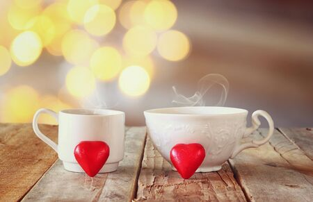 cafe bombon: image of tow red heart shape chocolates and couple cups of coffee on wooden table in front of bokeh glitter abstract background. valentines day celebration concept