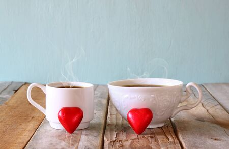 valentine          s day candy: image of tow red heart shape chocolates and couple cups of coffee on wooden table. valentines day celebration concept. vintage filtered Stock Photo