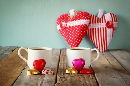 cafe bombon: imagen del remolque corazón rojo chocolates de forma y par de tazas de café en la mesa de madera. celebración concepto día de San Valentín. vendimia filtrada
