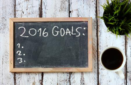 OBJETIVOS: vista desde arriba de la pizarra con la frase de 2016 goles en la tabla de madera con café