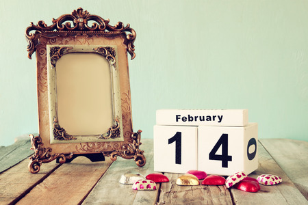 14th: February 14th wooden vintage calendar with colorful heart shape chocolates next to blank vintage frame on wooden table. selective focus.Template ready to put photography