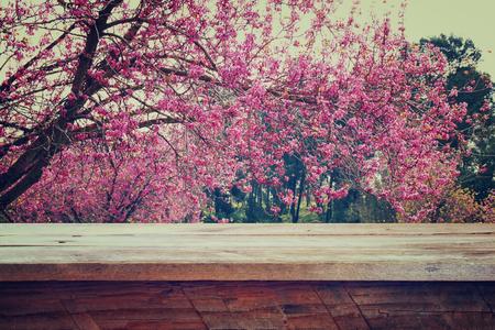 fleur de cerisier: table rustique en bois devant printemps Fleurs de cerisier arbre. rétro image filtrée. l'affichage des produits et le concept de pique-nique