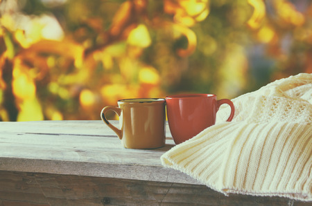 cups of coffee: front image of two coffee cups over wooden table and woolen sweater in front of autumnal sunset background. Valentines Day concept