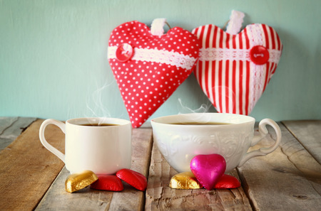 valentine          s day candy: image of two red heart shape chocolates and couple cups of coffee on wooden table. valentines day celebration concept. vintage filtered