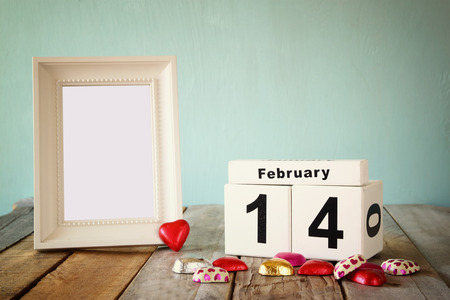 february 14th: February 14th wooden vintage calendar with colorful heart shape chocolates next to blank vintage frame on wooden table. selective focus.Template ready to put photography. retro filtered Stock Photo