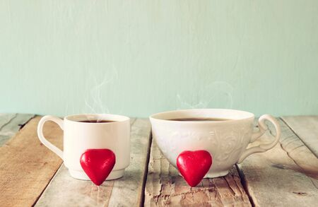 cafe bombon: image of two red heart shape chocolates and couple cups of coffee on wooden table. valentines day celebration concept. vintage filtered