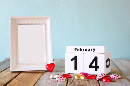 14th: February 14th wooden vintage calendar with colorful heart shape chocolates next to blank vintage frame on wooden table. selective focus.Template ready to put photography. retro filtered Stock Photo