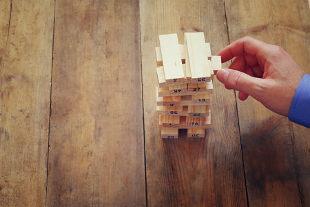 investment strategy: top view of male hand placing wooden block on a tower. planing and strategy concept Stock Photo