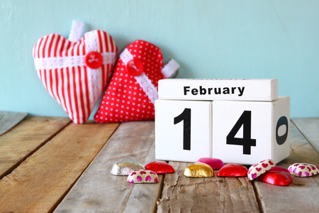 february 14th: February 14th wooden vintage calendar with colorful heart shape chocolates on wooden table. selective focus. vintage filtered